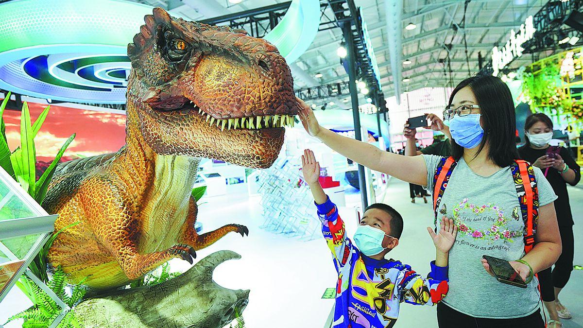Los visitantes tocan un modelo de dinosaurio en la Feria Internacional de Comercio de Servicios de China en el Parque Shougang en Beijing, el 4 de septiembre. CHEN YEHUA / XINHUA