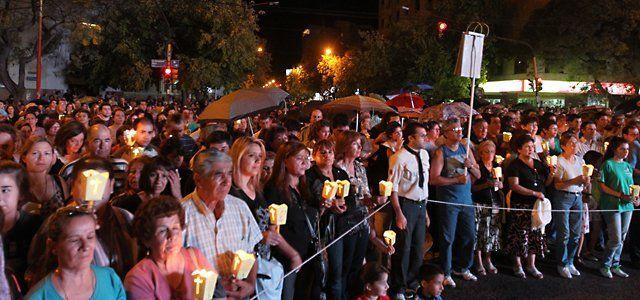 Una multitud de fieles católicos bajo la lluvia en el Vía Crucis