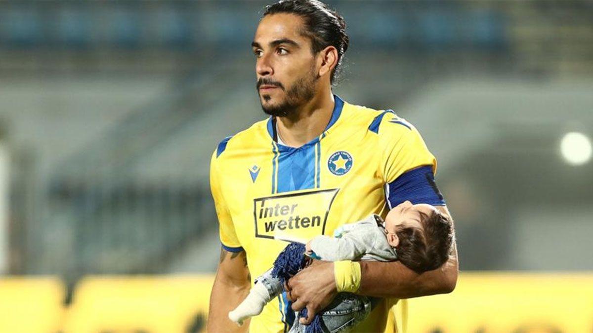 Matías lleva a su bebé en brazos en la cancha.