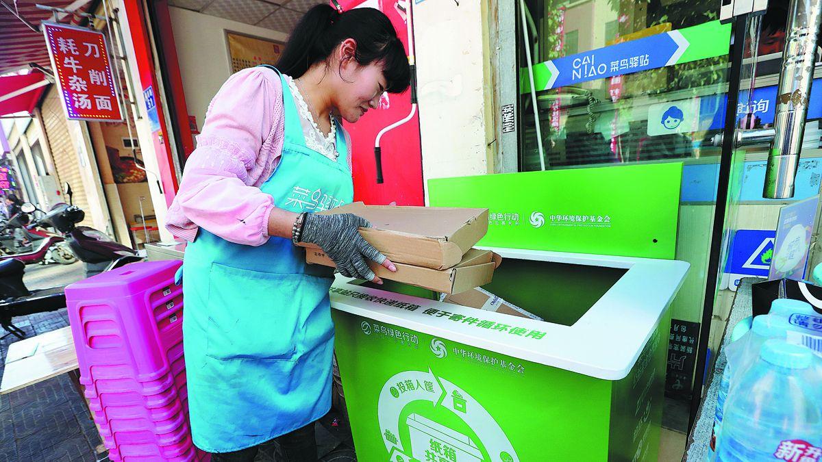 Una mujer arroja cajas de entrega vacías en un contenedor de reciclaje en una comunidad en Kunming