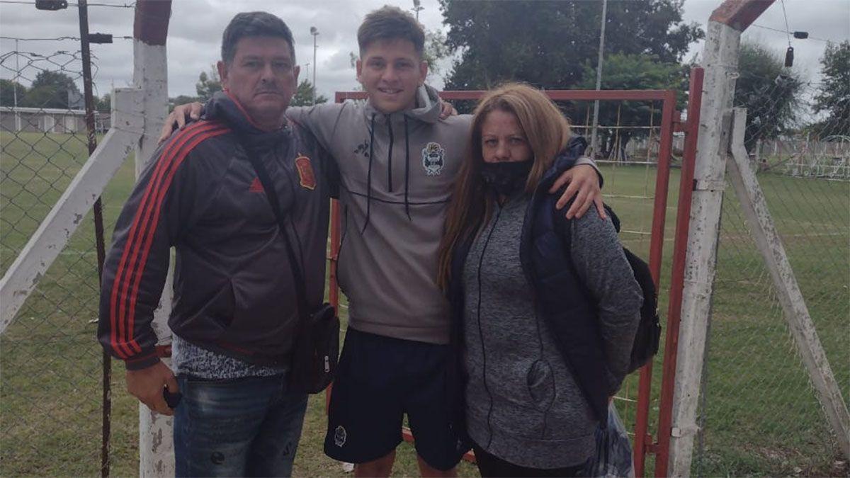 Matías está abrazado con sus padres.