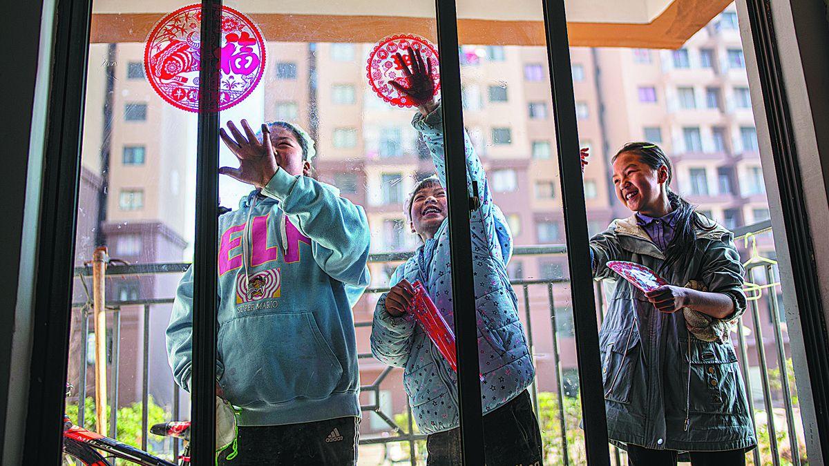 Una familia colocó calcomanías para la Fiesta de Primavera en su nuevo hogar en la ciudad de Qujing
