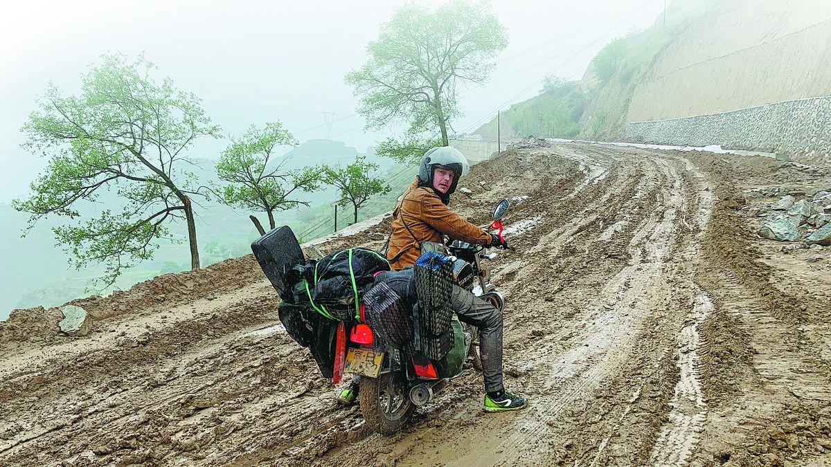 Mads Nielsen (en la imagen) y su compañero Anthony Tao recorrieron caminos de barro en las laderas de las montañas. PARA USO DE CHINA DAILY
