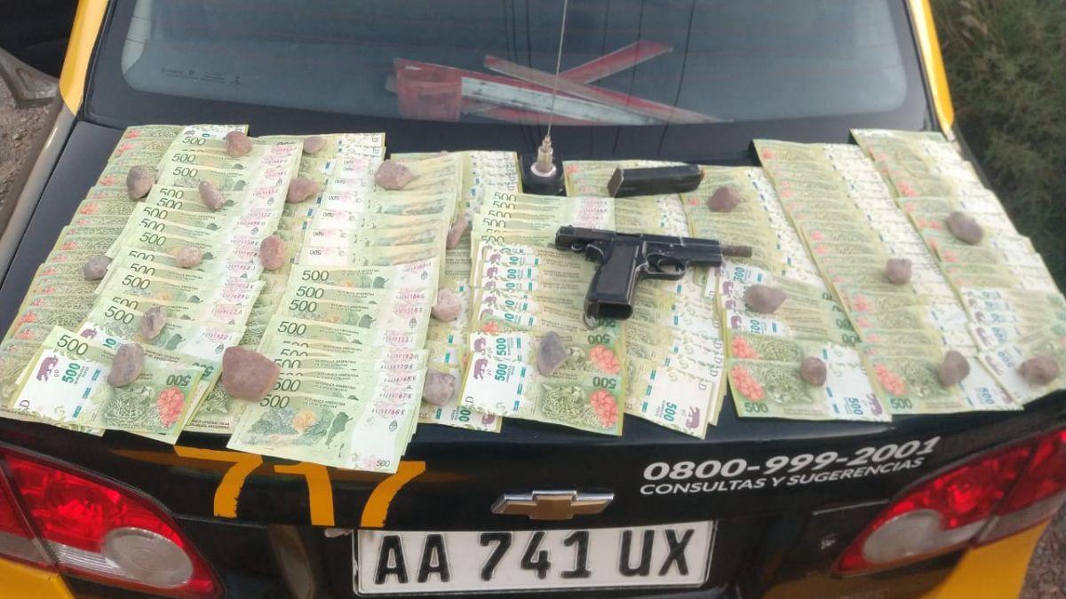 Sobre el baúl del taxi que transportaba a un sospechoso se exhibió el dinero y la pistola encontrada entre las pertenencias del pasajero que quedó detenido en el Oeste de Godoy Cruz.