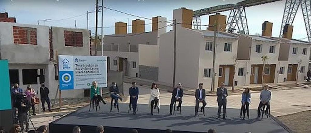 Captura de la transmisión oficial en la que se confirma la presencia de las viviendas sin terminar junto con el cartel que anuncia la terminación de las 84 viviendas.