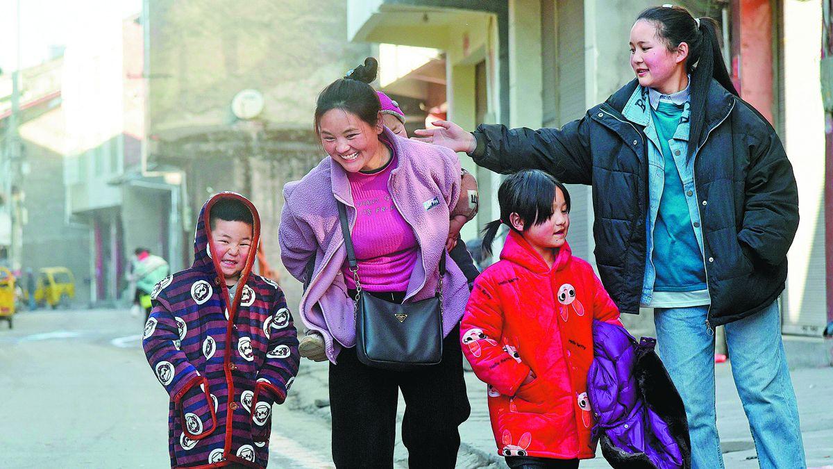 Bamuyubumu y sus hijos caminan por una calle de su ciudad natal en la prefectura autónoma de la etnia yi de Liangshan