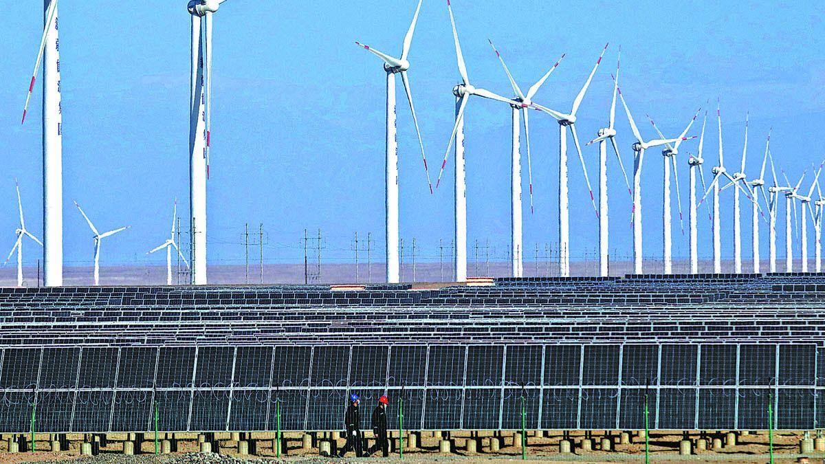 Los trabajadores patrullan una planta de energía eólica y fotovoltaica en Hami
