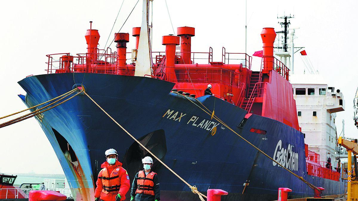 Empleados pasan delante de un barco en el puerto de Dongjiakou en Qingdao