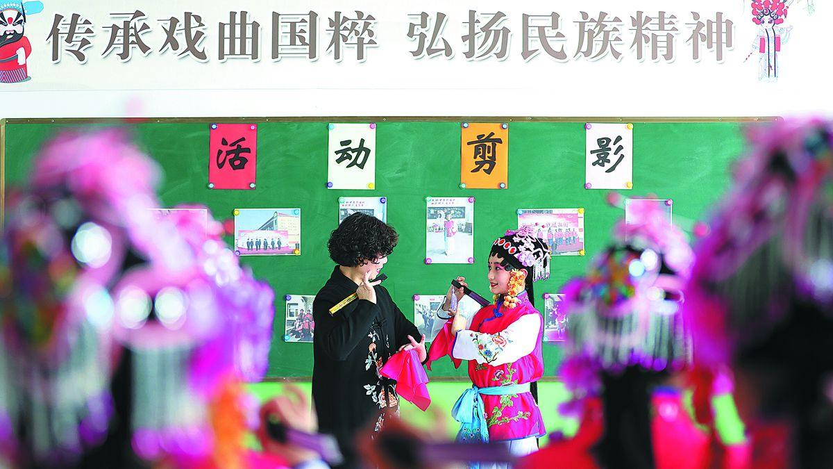 Una profesora da indicaciones a una alumna durante una clase sobre los conceptos básicos de la Ópera de Pekín en una escuela primaria en el condado de Longyao