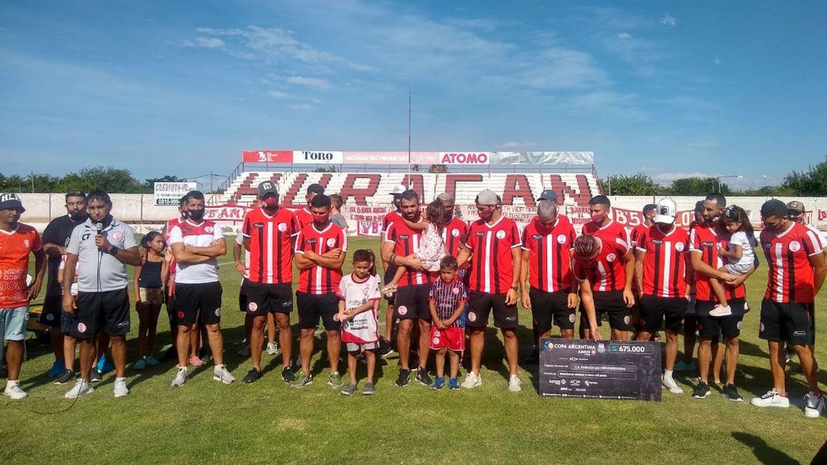 Los jugadores y el cuerpo técnico de Huracán lucieron el cheque ganador. (Fotos prensa HLH).
