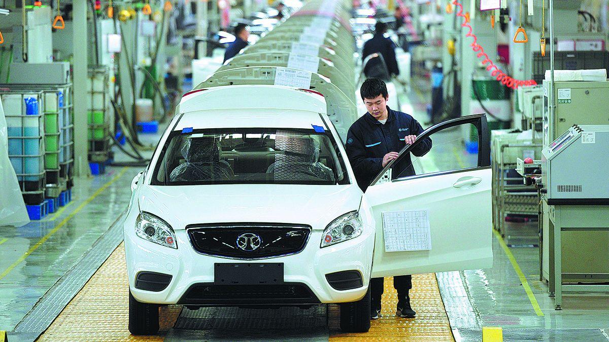 Los técnicos trabajan en la línea de montaje de Beijing Electric Vehicle Co en Huanghua